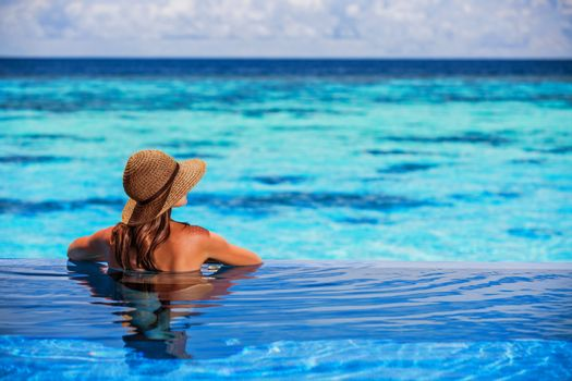 Having fun on beach resort, back side of sexy woman enjoying seascape from the pool, luxury summer vacation, travel and tourism concept
