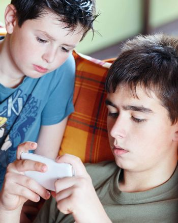 Teenager boys playing on smartphone, outdoor