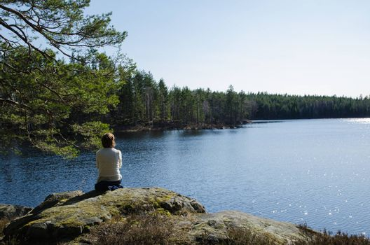 Woman at glittering forest lake