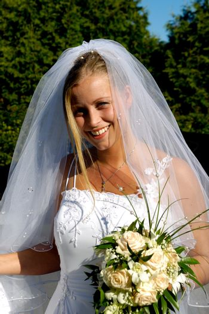 Happy smiling wedding bride with bouquet.