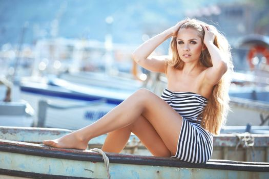 Beautiful sexy model posing on vintage boat at summer beach