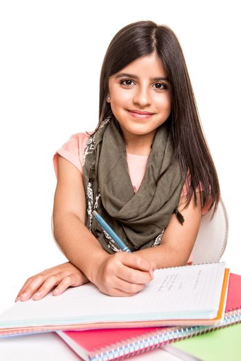 Cute little girl studying and smiling on desk