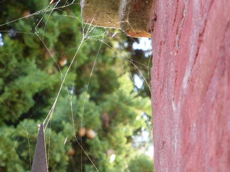 Spiderweb between iron cape and old wall in the sunlight