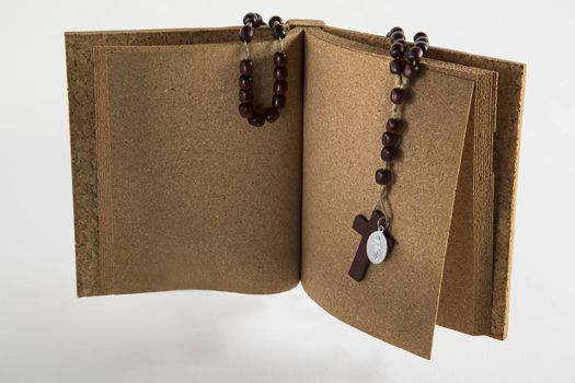 Rosary beads necklace on opened cork book
