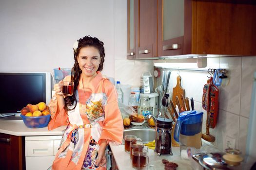 young girl with cup of tea in the kitchen