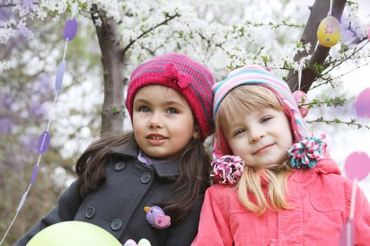 Pretty girls together holding painted egg outdoor in spring