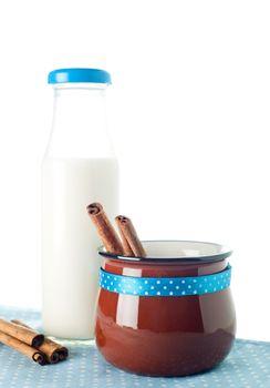 Brown mug, milk bottle, cinnamon on blue napkin