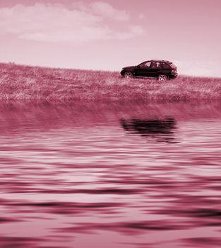 Car on the meadow near a lake.