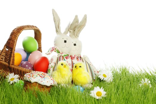 Easter card with eggs in basket and toy rabbits on green grass