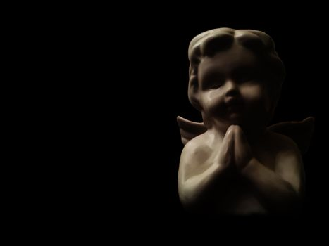 Angel praying in the dark, with copyspace