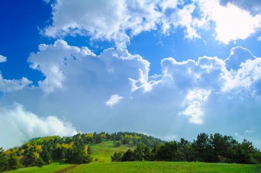 Fantastic Cloudy Sky over the Forest and Hill