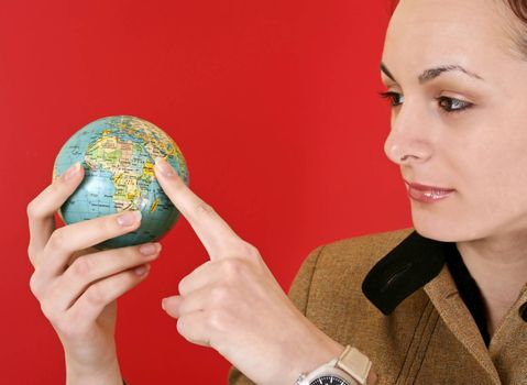 Globe in a girl's hands. Isolated on red