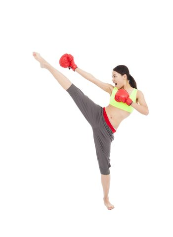 pretty female boxer  is kicking and punching