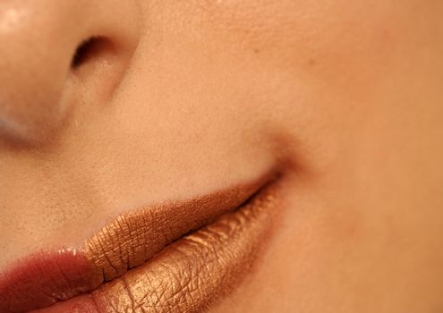 Macro image of bright lips. Red and gold lipstik