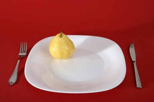 Tasty  yellow pear on a white plate.