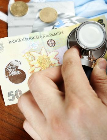 Recession concept: money and a stethoscope. Close up shoot.