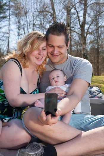 Young family is taking a selfie picture with their smartphone