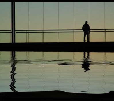 man in the building, with water reflection