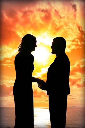 young loving couple holding hands in silhouette at sunset gazing into each others eyes