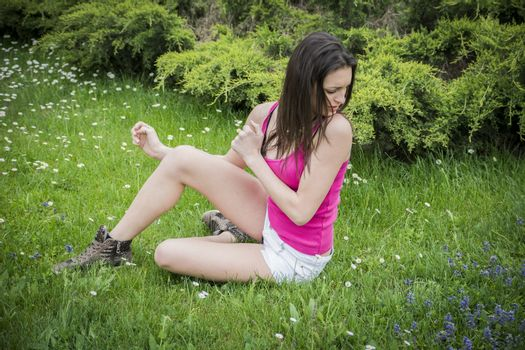 Attractive young woman on grass scared by insects