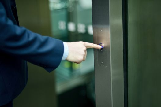 Hand pressing elevator button