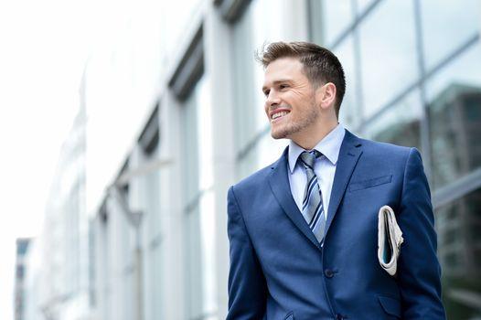 Handsome businessman holding a newspaper