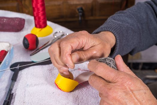 Old male hands sewing traditional jai alai balls