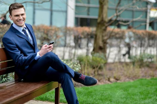 Businessman with his phone on the bench