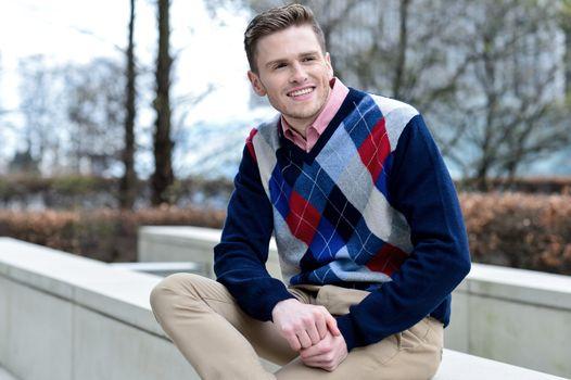 Stylish young man sitting in sidewalk