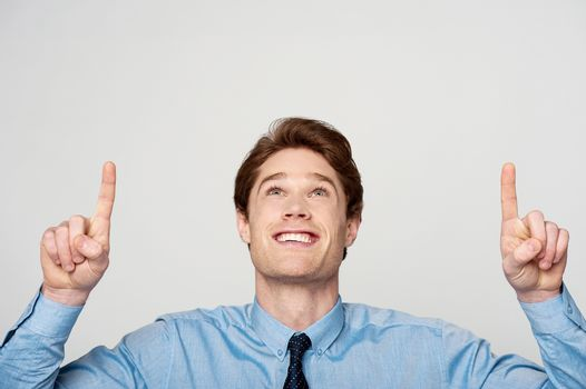 Young male executive pointing up