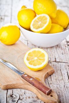 fresh lemons in a bowl and knife