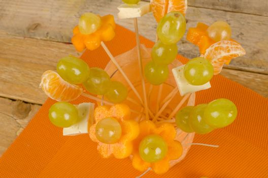 Assorted fruit and cheese decorated to make it attractive for kids