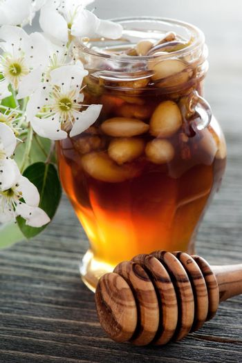 Honey in a jar with different nuts on a dark wooden table