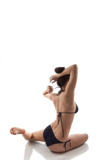 Young woman doing stretching exercises isolated on white background. Yoga, asana, healthy lifestyle. Beauty, caucasian brunette with long hair.