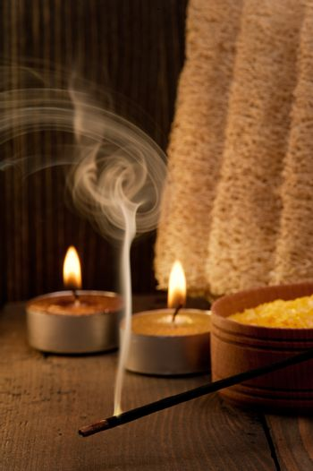 Spa setting and fuming aroma stick on dark wooden background