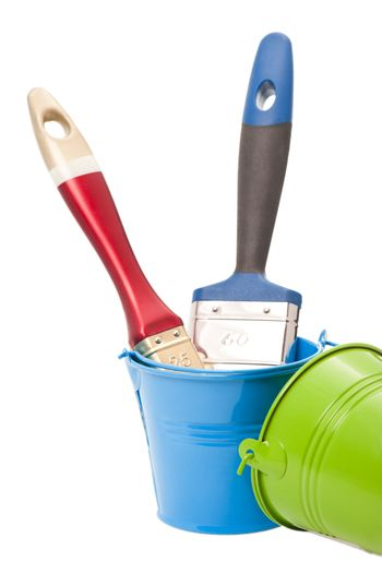 Paint brushes in green and blue tin buckets isolated on white