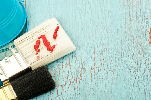 Paint brushes on a shabby blue wooden background