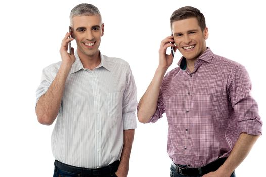 Smiling young men with cell phones