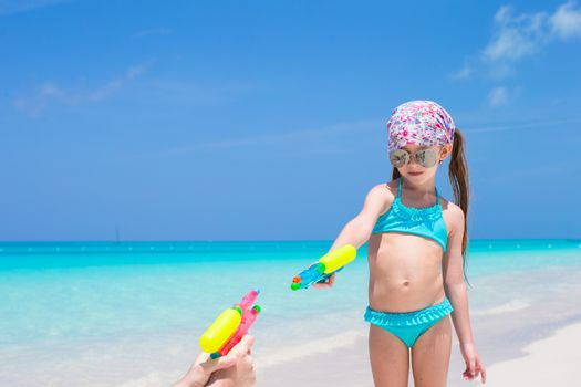 Little girl play with water pistol on tropical beach