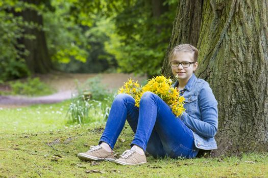 Smiling girl with big bouquet of spring flowers sitting in the park