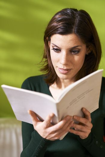 girl studying literature with book at home