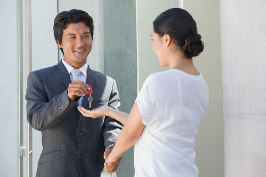 Smiling estate agent giving the key to buyer