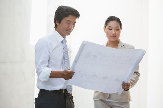 Estate agent and buyer looking at blueprint