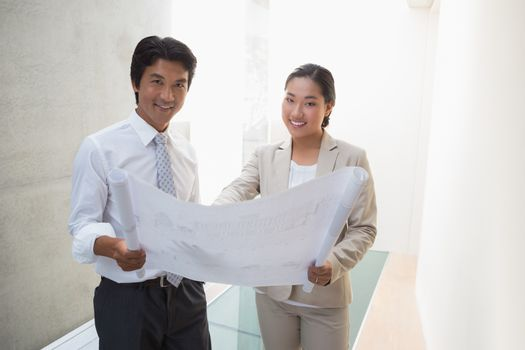 Estate agent looking at blueprint with potential buyer