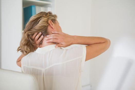 Casual businesswoman rubbing her neck
