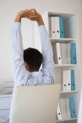 Casual businessman stretching in swivel chair