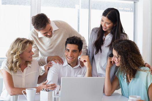 Casual smiling business team congratulating their colleague