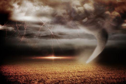 Stormy sky with tornado over field