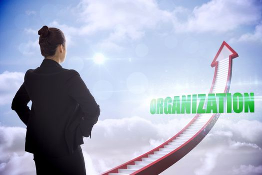 Organization against red stairs arrow pointing up against sky