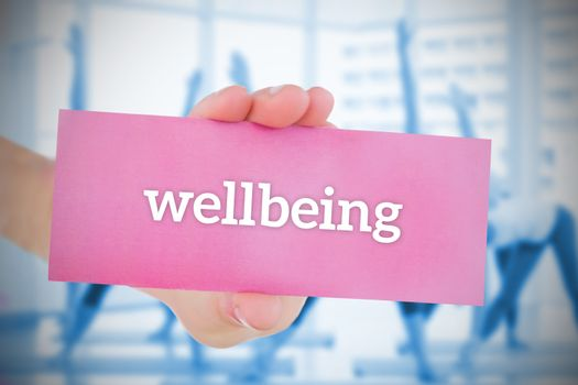 Woman holding pink card saying wellbeing